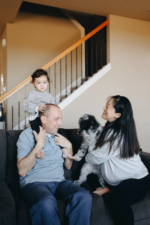 A Happy Family Sitting On Gray Sofa With Their Dog