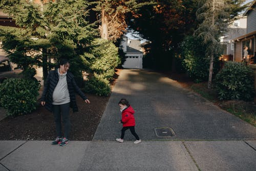 Mother And Child Walking On Sidewalk
