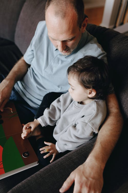 Father Holding A Book Beside His Child