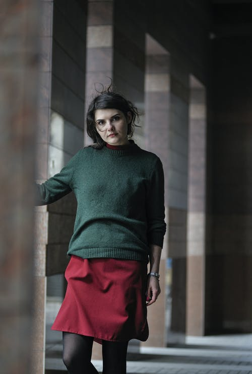 Woman in Green Turtleneck Sweater and Red Skirt Standing