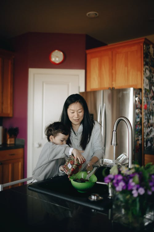 Mother And Child Putting Strawberries In A Bowl