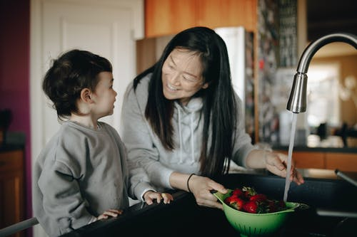 Mother And Child Washing A Bowl Of Strawberries