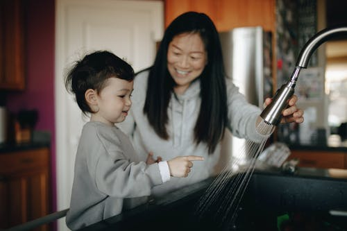 Mother And Child Standing Infront Of A Kitchen Sink