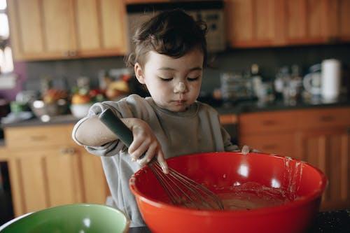 Мальчик в серой футболке с круглым вырезом держит красную пластиковую миску с серебряной ложкой
