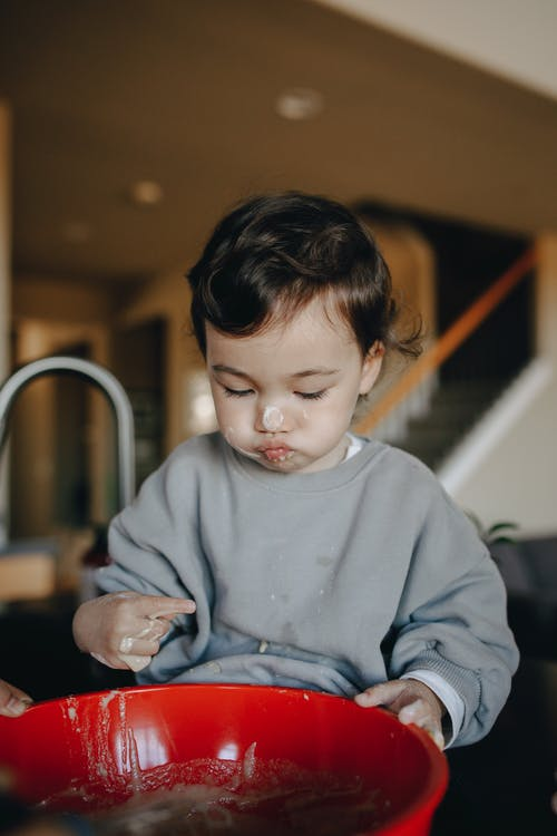 A Child Playing With Mixture On A Bowl