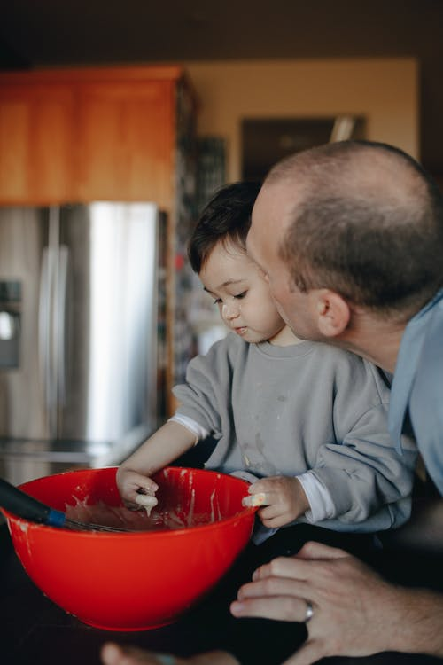 Child Playing With Batter In A Mixing Bowl Beside Her Father