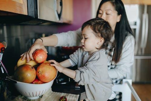 Boy in White Long Sleeve Shirt Holding Red Apple Fruit