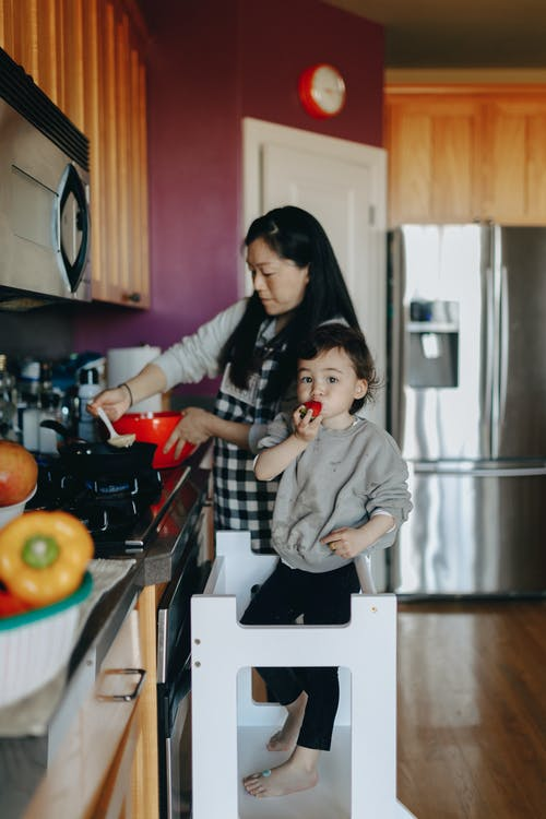 Woman Cooking With Her Little Girl Beside Her
