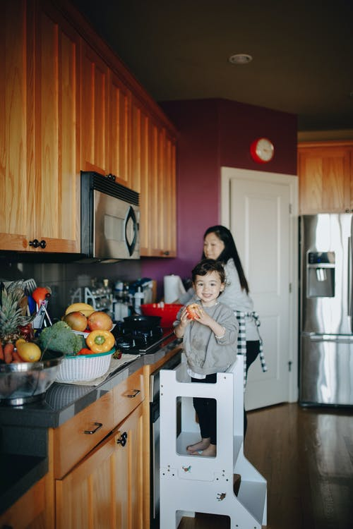 Adorable Child Standing On A Stool In The Kitchen With Her Mother