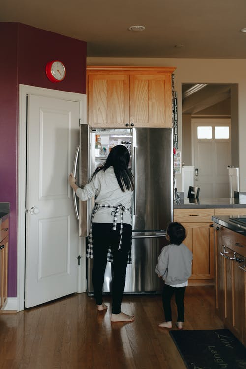 Mother And Child Standing Infront Of An Open Refrigerator