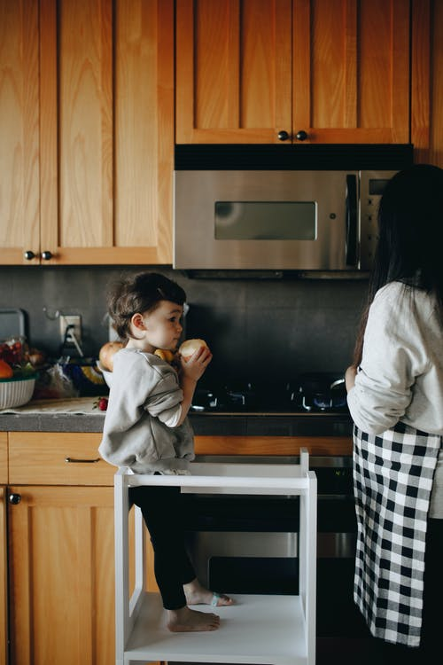 Adorable Child Standing Beside Her Mother In The Kitchen