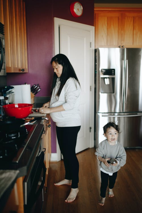 Woman Doing Chores In The Kitchen With Her Child