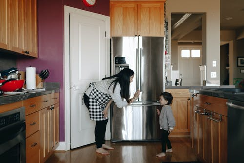 Mother And Daughter Standing Infront Of A Refrigerator