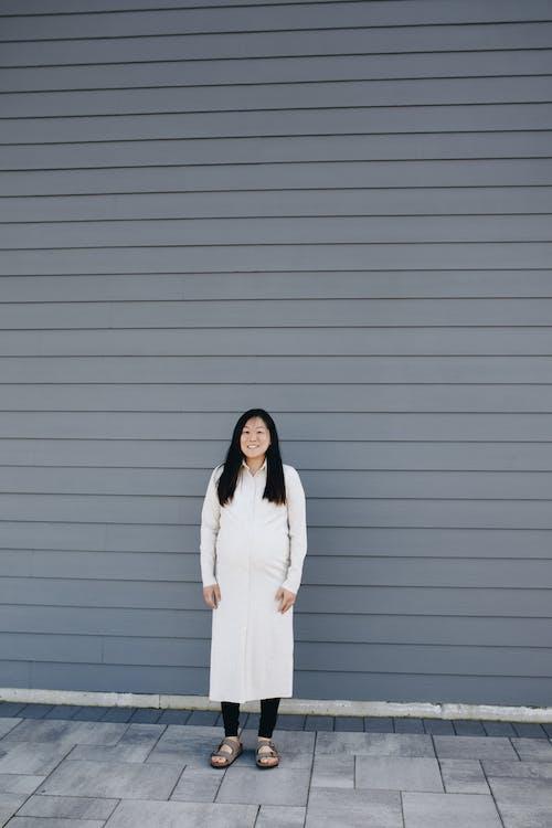 Woman Standing Near A Gray Wall