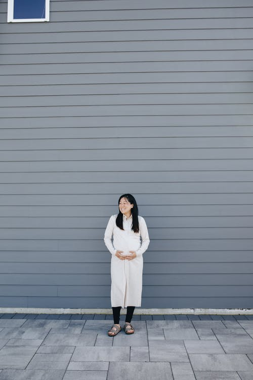 Pregnant Woman Standing Beside A Gray Wall