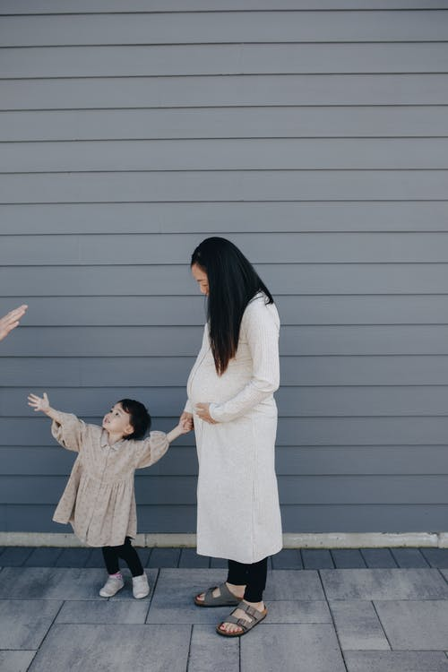 Mother And Child Standing Beside A Gray Wall