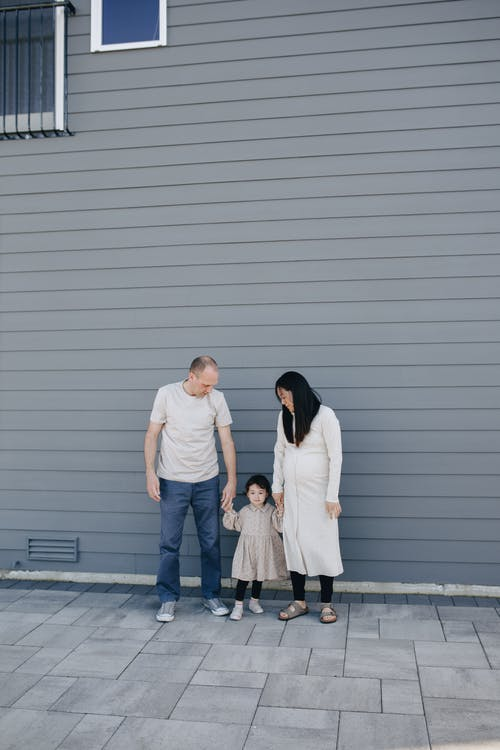 A Family Standing Beside A Gray Wall