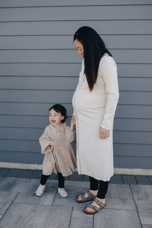 Mother And Daughter Standing Near A Gray Wall