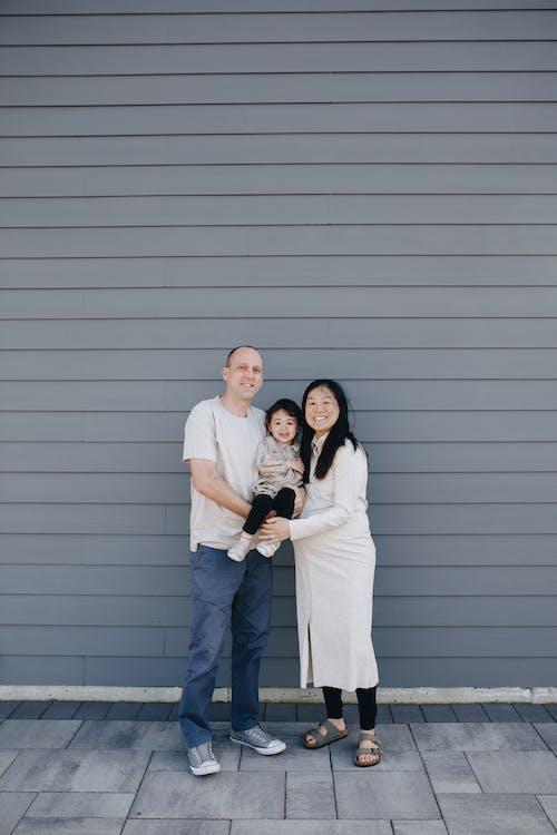 Happy Family Standing Near A Gray Wall