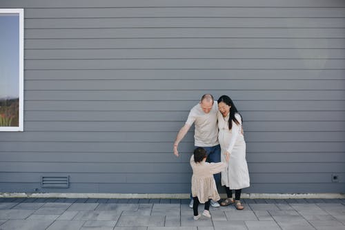 Happy Family Standing Beside A Gray Wall