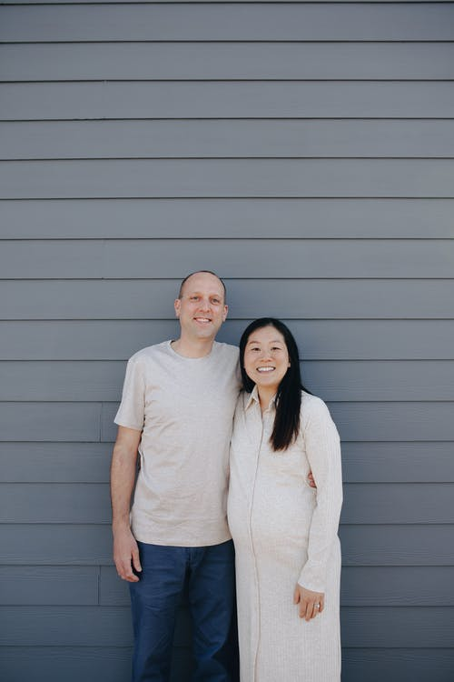 Couple Standing Near A Gray Wall
