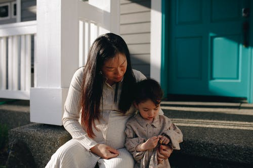Woman And Child Sitting On The Steps To The Porch