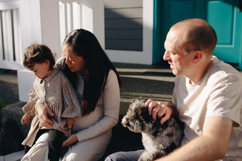 Family Sitting On The Steps To A Porch