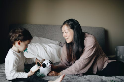 Mother and Baby Playing with White and Black Dog Plush Toy