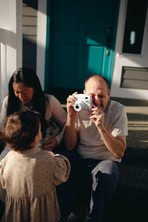 Man Taking A Photo Of His Baby Girl With An Instant Camera