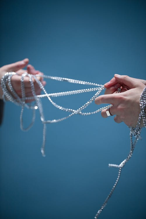 Person Holding White and Blue Beaded Necklace