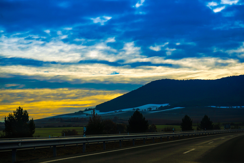 Kostenloses Stock Foto zu asphalt, bäume, berge, goldene stunde