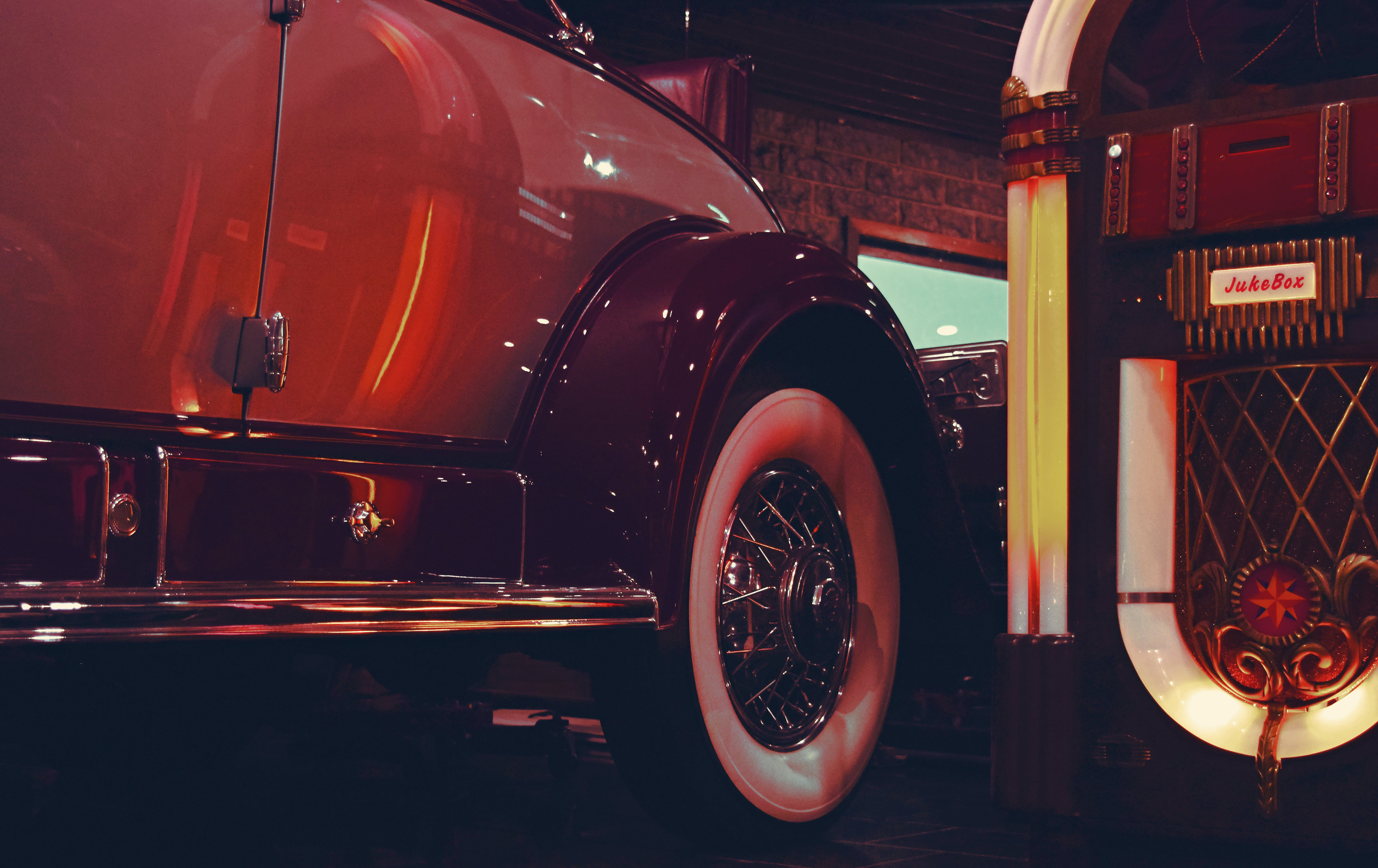 Lighted Jukebox Beside White and Brown Car