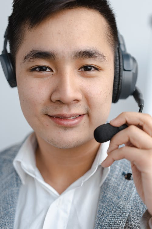 Man Smiling and Holding Microphone of the Headset