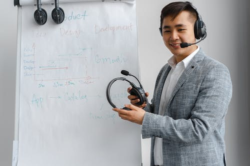 Man in Gray Suit Smiling and Holding Black Headphones near Paper Board