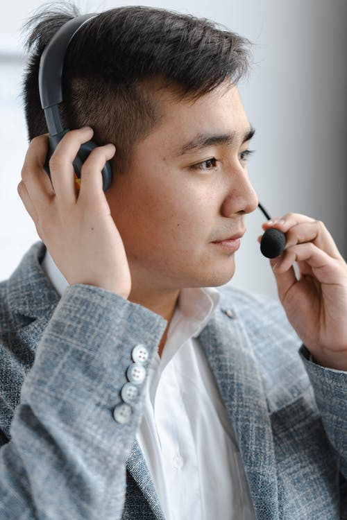 Man in Gray Plaid Jacket Holding Headset