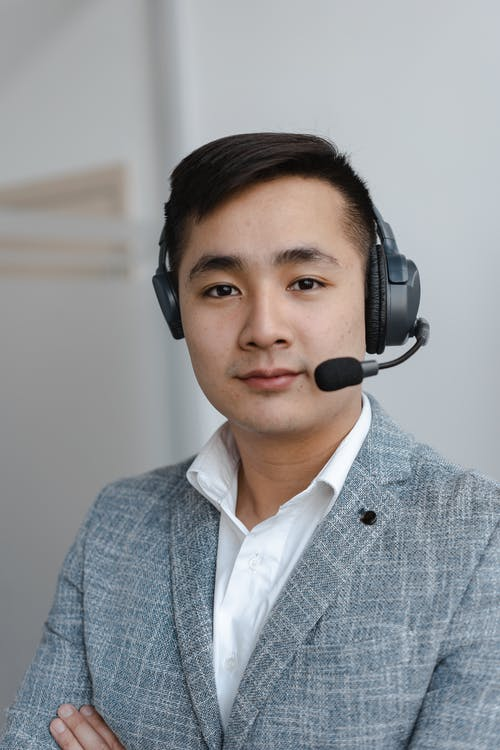 Man in Gray Suit Wearing Black Headphones