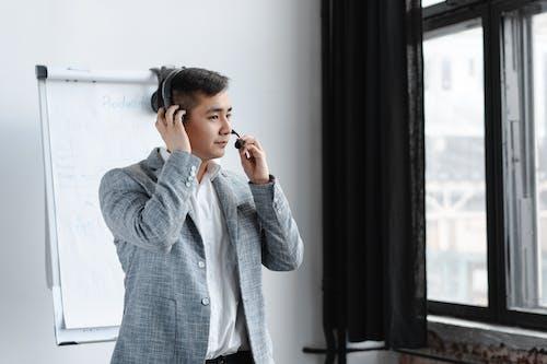 Man in Gray Suit ad Headphones Standing Near Window