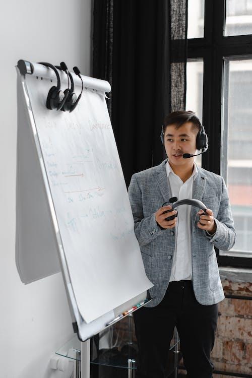 Man Holding Headset Near Paper Board