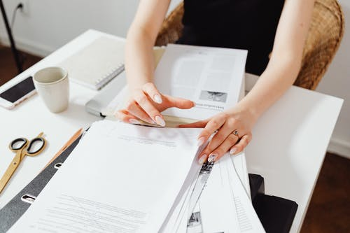 Close-Up Photo of Person Doing Paperwork