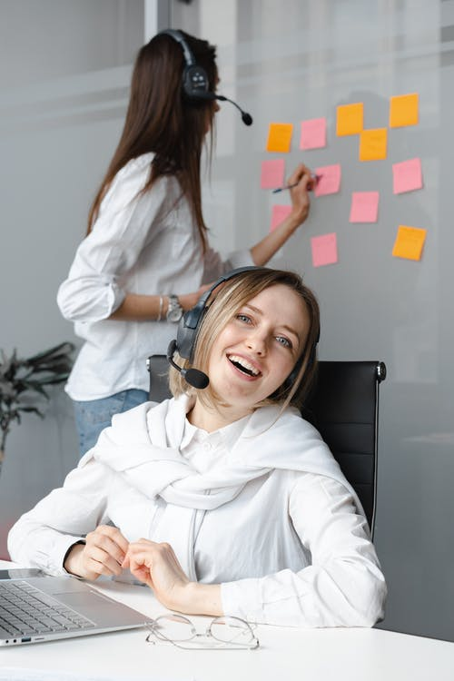 Smiling Woman in White Long Sleeve Shirt Working as a Call Center Agent