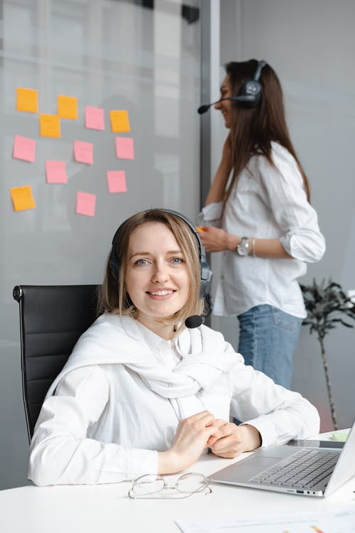 Woman in White Long Sleeve Shirt Working as a Call Center Agent