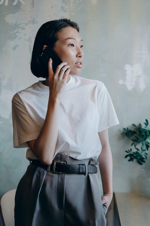 Woman in White Shirt Having Phone Call