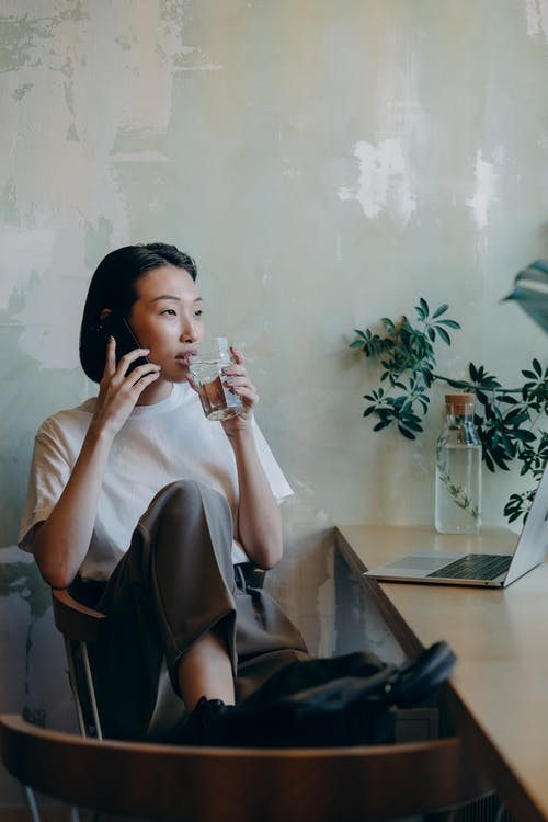 Woman in White Shirt Sitting on Chair while Having Phone Call