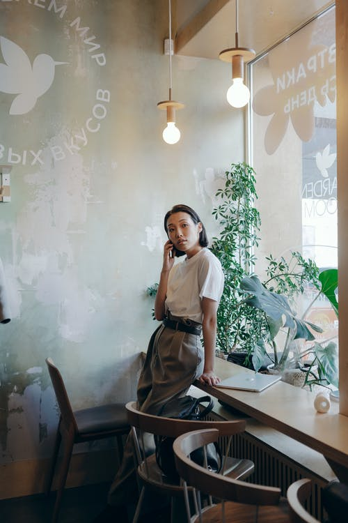 A Businesswoman Having a Phone Call Inside the Coffee Shop