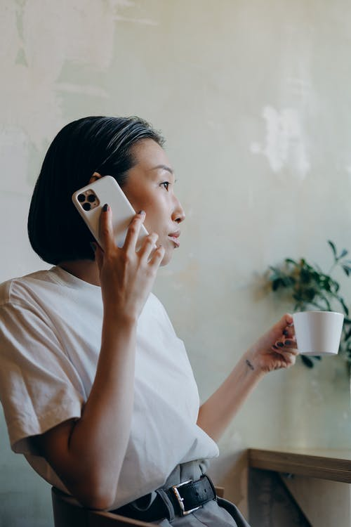 Woman in White Shirt Holding a Cup while Having Phone Call