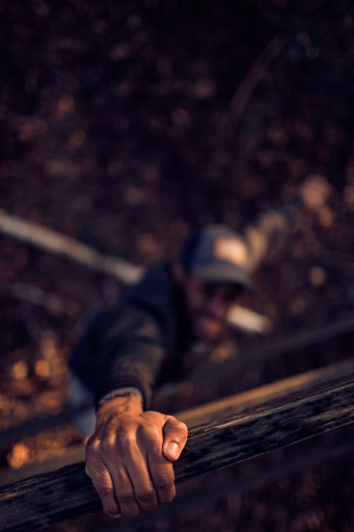 Man Holding On Wood