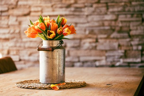 Yellow Flowers in White Ceramic Vase on Brown Wooden Table