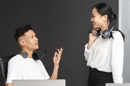 Man and Woman in White Clothes Wearing Headset