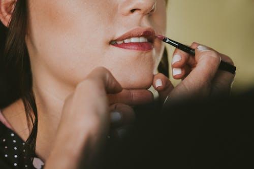Crop professional makeup artist with brush applying stylish lipstick on female model lips in light studio