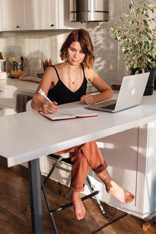 Concentrated female in casual outfit sitting on chair at table while working on netbook and writing information in notebook with pen in bright kitchen